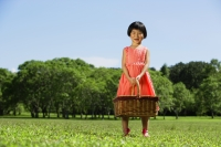 Girl standing in park, holding picnic basket - Alex Mares-Manton