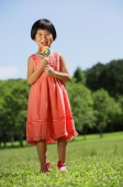 Girl standing in park, licking lollipop - Alex Mares-Manton