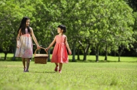 Girls walking in park, carrying picnic basket - Alex Mares-Manton