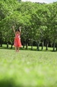 Girl walking in park, arms outstretched, smiling - Alex Mares-Manton