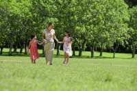Mother and two daughters holding hands, walking across park - Alex Mares-Manton