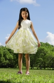Girl wearing dress, standing in park, smiling at camera - Alex Mares-Manton