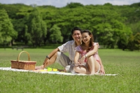Couple sitting in park, having a picnic, looking at camera - Alex Mares-Manton