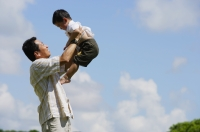 Father lifting son in the air, side view - Alex Mares-Manton