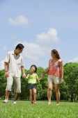 Family with one child walking in park, holding hands - Alex Mares-Manton
