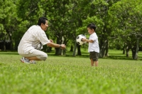 Father and young son in park with soccer ball - Alex Mares-Manton