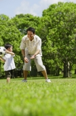 Father and young son playing with soccer ball in park - Alex Mares-Manton