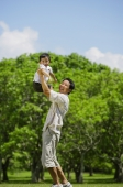 Father lifting son in the air, both looking at camera - Alex Mares-Manton