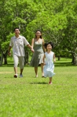 Mother and father holding hands, walking, daughter running in foreground - Alex Mares-Manton