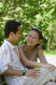 Mature couple sitting on bench, looking at each other - Alex Mares-Manton