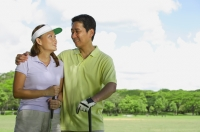 Couple standing side by side, holding golf clubs, looking at each other - Alex Mares-Manton
