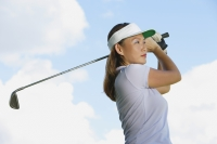 Woman wearing sun visor, swinging golf club - Alex Mares-Manton