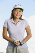 Woman wearing sun visor, leaning on golf club - Alex Mares-Manton