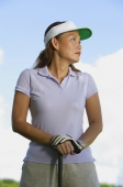 Woman wearing sun visor, leaning on golf club, looking away - Alex Mares-Manton