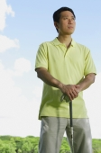 Man standing, leaning on golf club, looking away - Alex Mares-Manton