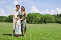 Family of three standing in field, looking at camera - Alex Mares-Manton