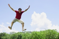 Man jumping in mid air, arms outstretched - Alex Mares-Manton