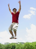 Man jumping in mid air, arms outstretched, smiling - Alex Mares-Manton
