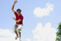 Man jumping in mid air, hand raised, mouth open - Alex Mares-Manton