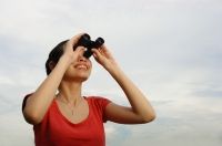 Woman using binoculars, smiling - Yukmin
