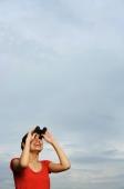 Woman looking through binoculars, smiling - Yukmin