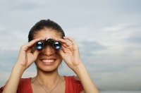 Woman looking through binoculars, head shot - Yukmin