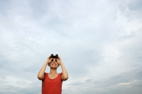 Woman with binoculars looking at sky - Yukmin