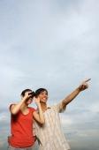 Woman looking through binoculars, man next to her pointing in the distance - Yukmin