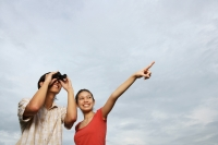 Man looking through binoculars, woman next to him pointing in the distance - Yukmin