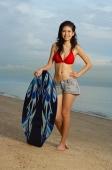 Young woman on beach, standing next to skimboard - Yukmin