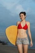 Young woman holding skimboard, smiling at camera - Yukmin