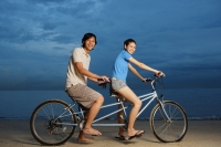 Couple on beach, sitting on tandem bicycle, smiling at camera - Yukmin