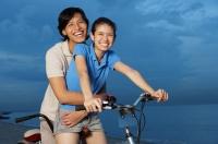 Couple on tandem bicycle, man embracing woman - Yukmin