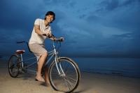 Man on beach, sitting on tandem bicycle - Yukmin