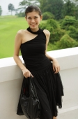 Young woman in black dress, leaning on ledge - Yukmin