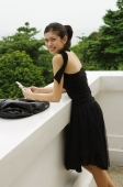 Young woman in black dress, leaning on ledge, holding mobile phone - Yukmin