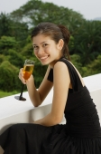 Young woman leaning on ledge, holding champagne glass - Yukmin
