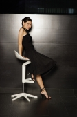 Young woman in black dress sitting on stool, looking at camera - Yukmin