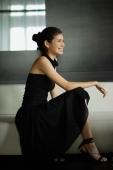 Young woman in black dress, crouching, looking away - Yukmin