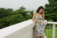 Young woman in floral dress, standing on balcony, using mobile phone - Yukmin