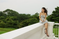 Young woman sitting on balcony ledge, looking away - Yukmin