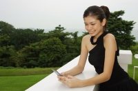 Young woman in black dress, leaning on ledge, looking at mobile phone - Yukmin