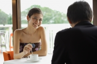 Young woman having coffee in restaurant, smiling at camera, man in the foreground - Yukmin