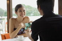 Couple in restaurant, man presenting woman with jewellery box - Yukmin