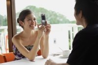 Couple in restaurant, woman using mobile phone to take a picture of man opposite from her - Yukmin
