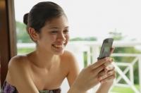 Woman using mobile phone, text messaging - Yukmin