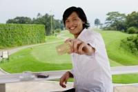 Man holding credit card, smiling at camera, golf course behind him - Yukmin