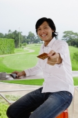Man holding credit card, towards camera, golf course behind him - Yukmin