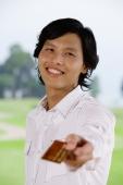 Man holding credit card, towards camera, smiling - Yukmin