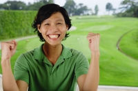 Man in green polo shirt, smiling at camera, hands raised as fists - Yukmin